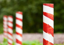 Red and white striped poles. In the row royalty free stock image