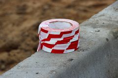 Red and white, striped protective tape for protect fresh asphalted road, repair work lies on the cement curb. Industrial artistic royalty free stock photos