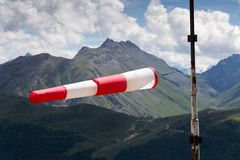 Red and white striped windsock dramatic clouds mountains in background Stock Image