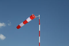 Red-white striped windsock on a pole. Flapping red and white striped windsock on a pole on the clear blue sky royalty free stock photo