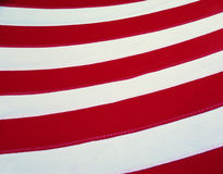 These are the red and white stripes from an American flag. They cross the image horizontally, curving up toward the right side. Stock Photos