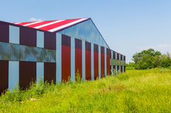 Red with white stripes building on the airfield field Stock Photos