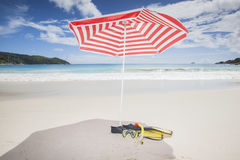 Red and white sunshade with diving equipment Stock Images