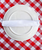 Red and white table cloth with plate. Napkin and utensils Royalty Free Stock Photography