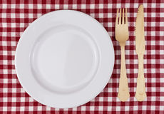 Red and white tablecloth with plate and cutlery Royalty Free Stock Photo