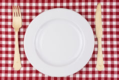 Red and white tablecloth with plate and cutlery Royalty Free Stock Images