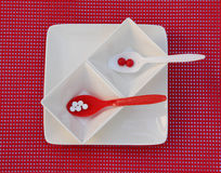 Red and White. Tablets and spoons on white and red plates and background Royalty Free Stock Photography