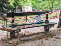 Red and white tape surround recently painted bench in Jardin de. Attention travaux de peinture sign hangs from red and white warning tape around a recently stock images