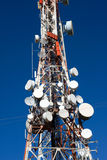 Red and White Telecom Mast. Red mobile phone masts with white antennas against blue sky Royalty Free Stock Photos