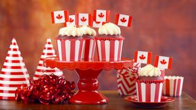 Red and white theme cupcakes with Canadian maple leaf flags. For first of July Canada Day or Canadian theme party food Royalty Free Stock Images