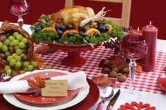 Red and white theme Thanksgiving table. Red and white theme Thanksgiving table with individual place setting, food and cornucopia Stock Image