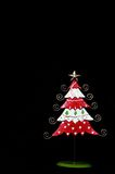 Red and white tin Christmas tree against black. Stock Photo