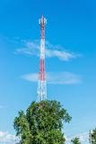 Red and white tower of communications with a lot of different antennas under clear sky. Royalty Free Stock Image