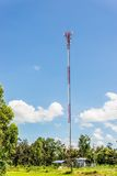 Red and white tower of communications with a lot of different antennas under clear sky. Stock Photo