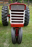Red White Tractor. Head on view of a vintage red and white farming tractor stock image