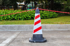 Red-white traffic cone and chain on street Royalty Free Stock Photography