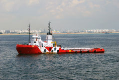 Red and white Tug boat in Singapore anchorage. Red and white tug boat seen towing a large barge in Singapore anchorage Royalty Free Stock Photos