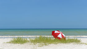 Red and white umbrella on beach Stock Photography