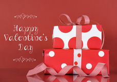 Red and white Valentine gifts with sample text. Happy Valentines Day stack of red and white gifts on red background with sample text greeting message Stock Photos
