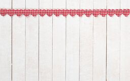 Red and White Valentines Day Hearts in a Row at the top of White Boards Background with copy space below.  It`s a wide horizontal