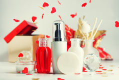 Red and white valentines day spa cosmetics background. Aroma sticks, cream, serum, soap and shampoo on table under heart shaped confetti. Gift box and flower Royalty Free Stock Image