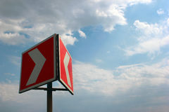 Red white warning arrow on blue sky background Stock Images