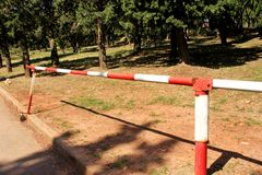 Red and white warning sign barrier on green grass in nature background. Transport, traffic regulation. Old fence made and white and red street parking barrier royalty free stock image