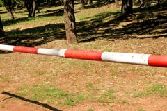 Red and white warning sign barrier on green grass in nature background. Transport, traffic regulation. Old fence made and white and red street parking barrier royalty free stock photo
