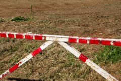 Red and white warning sign barrier on green grass in nature background. Transport, traffic regulation. Old fence made and white and red street parking barrier stock image