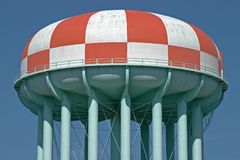 Red and white watertower. Water tower painted in a red and white checkerboard pattern Stock Photo
