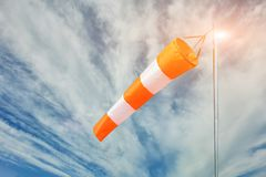 Red and white wind sock on blue sky and clouds background. Close-up royalty free stock images