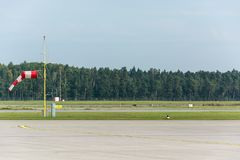 Red and white windsock at an airport runway Stock Photo