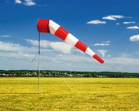 Red and white windsock on blue sky on the aerodrome, yellow field and clouds background. Red and white windsock wind sock on blue sky on the aerodrome, yellow stock image