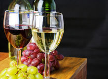 Red and white wine. With grapes and black background stock photos