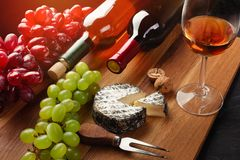 Red and white wine bottles with bunch of grapes, cheese head, nuts and wineglass on wooden board and black background.  stock image