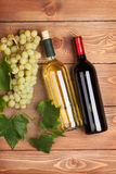 Red and white wine bottles and bunch of grapes Royalty Free Stock Photography