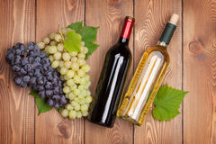 Red and white wine bottles and bunch of grapes Royalty Free Stock Photo