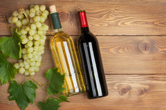 Red and white wine bottles and bunch of grapes Stock Images
