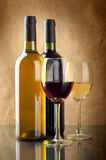Red and white wine. In bottles and wineglasses on linen background Stock Images