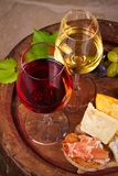 Red and white wine with cheese, prosciutto and grape on old wine barrel in cellar. Food and drinks concept. View from above, top, vertical royalty free stock image
