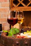 Red and white wine with cheese, prosciutto and grape on old wine barrel in cellar. Food and drinks concept, vertical stock photos
