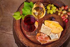 Red and white wine with cheese, prosciutto and grape on old wine barrel in cellar. Food and drinks concept. View from above, top, horizontal royalty free stock photo