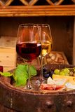 Red and white wine with cheese, prosciutto and grape on old wine barrel in cellar. Food and drinks concept, vertical stock image
