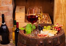Red and white wine with cheese, prosciutto and grape on old wine barrel in cellar. Food and drinks concept stock photography