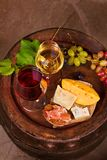 Red and white wine with cheese, prosciutto and grape on old wine barrel in cellar. Food and drinks concept. View from above, top, vertical stock image