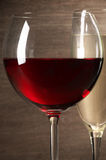 Red and white wine close-up. Glasses of red and white wine close-up on wooden background. Shallow DOF stock photography