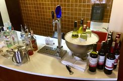 Red, white wine, draft beer and hard liquor. At bar counter of executive lounge in a hotel or airline lounge. The white wine is chilled in large stainless steel Stock Photos