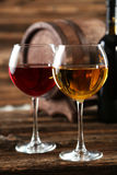 Red and white wine glass with bottle and barrel on a black background Stock Image