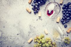 Red and white wine. With glass, bottle and grapes over gray stone background, copy space , top view stock photography