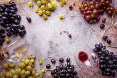 Red and white wine. With glass, bottle and grapes over gray stone background, copy space , top view stock images